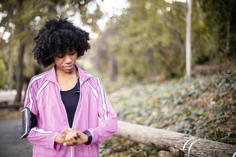 young black woman walking with smart watch