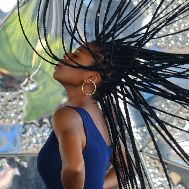 young black woman with very long braids and very attractive and sensual enjoying barcelona in summer and doing model with mobile, glasses and camera, technology concept.