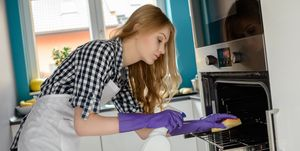 Young blond woman washes the oven