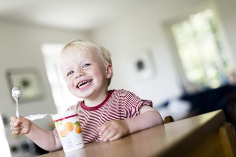 Young boy, 2 years, eating happily a yoghurt.