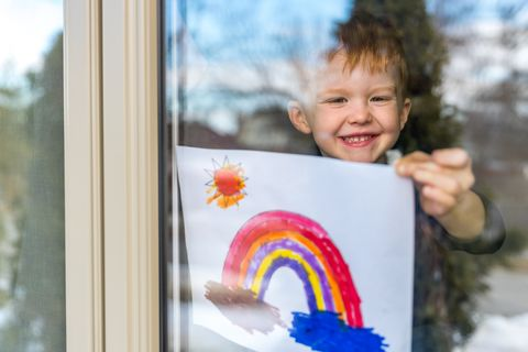 young boy sticking his drawing on home window during the covid 19 crisis