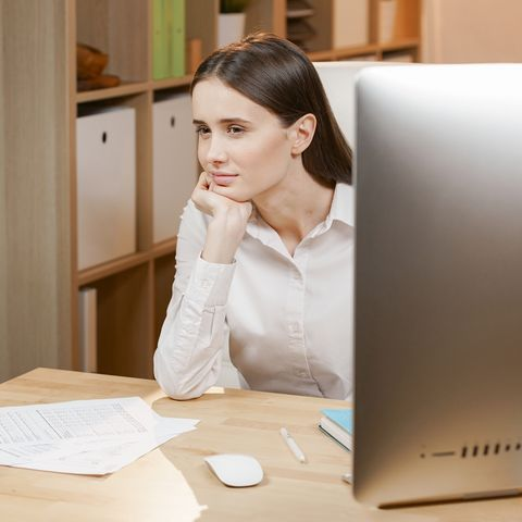 Young business woman thinking daydreaming sitting at desk with computer
