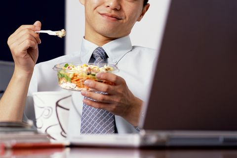 Young businessman eating  lunch at desk, looking at laptop