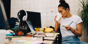 Young businesswoman drinking coffee while sitting at desk in small creative office