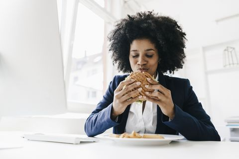 young businesswoman eating hamburger at her desk