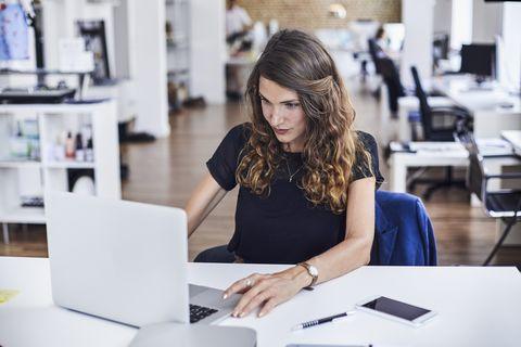 Mujer sentada en escritorio frente a ordenador