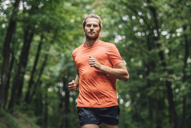 young caucasian sportsman running in the forest