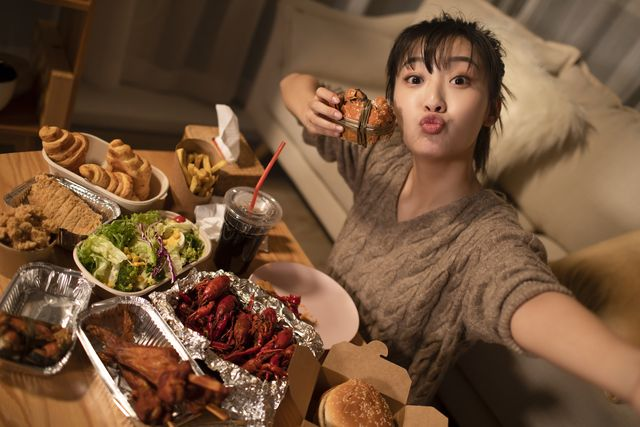 young chinese woman eating take out food at night