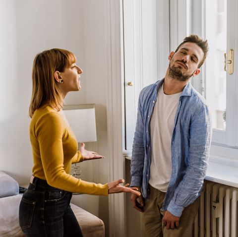 young couple arguing while standing at home