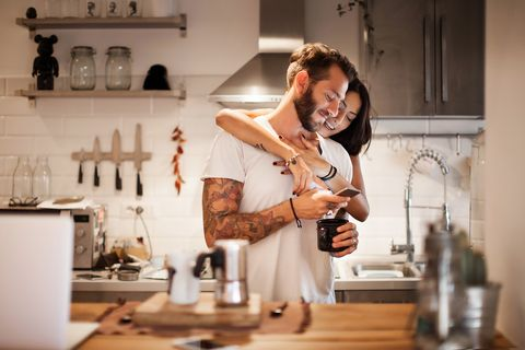 young couple at home using smartphone   morning breakfast time