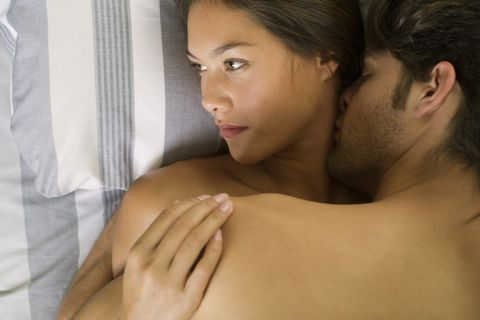 Young couple being intimate in bed, woman looking away