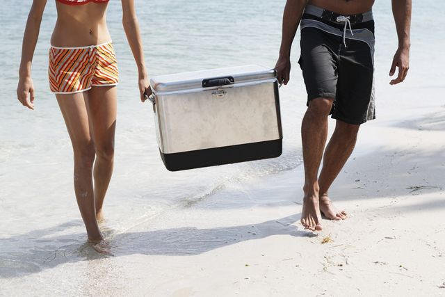 young couple carrying cooler on beach, low section