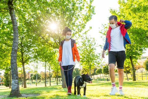 young couple during pandemic isolation walking with her dog in park