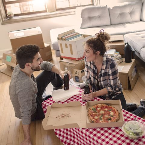 winter date ideas -  young couple eat pizza in new home, surrounded by boxes