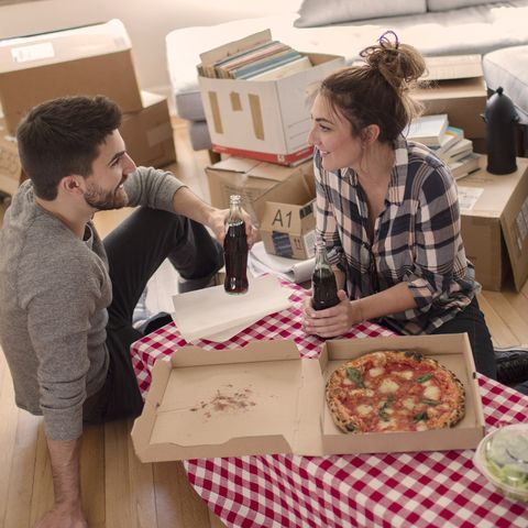 Moving house: Young couple eat pizza in new home, surrounded by boxes