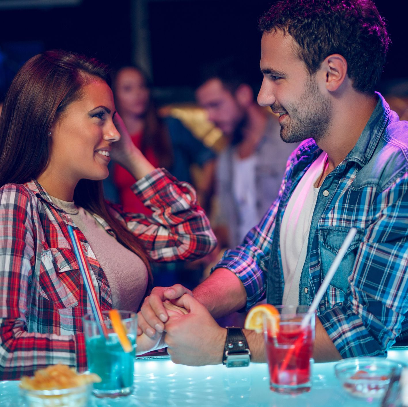 Young couple happily flirting over drinks at  night club