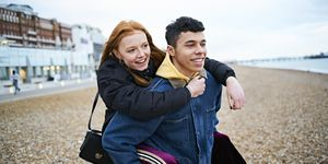 Young couple having fun together on the beach, the boyfriend giving the girlfriend a piggy-back both smiling and enjoying their time together