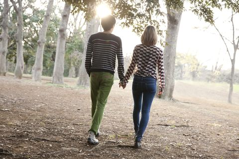 Young couple holding hands in park,rear view