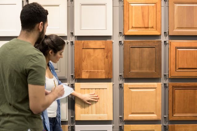 young couple look at cabinet samples in home improvement store