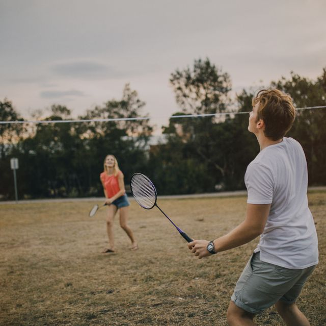 young couple playing badminton in the park