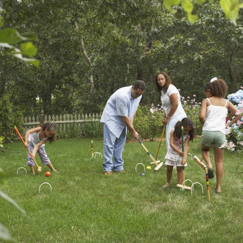 young couple playing croquet with their three daughters