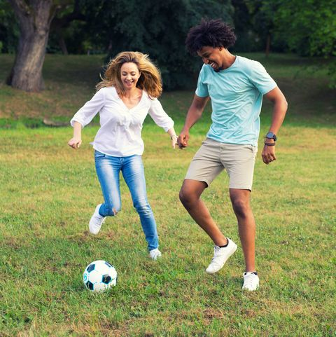 young couple playing soccer in the nature