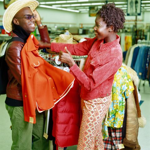 winter date ideas -Young couple shopping in thrift store, man trying on hat, side view
