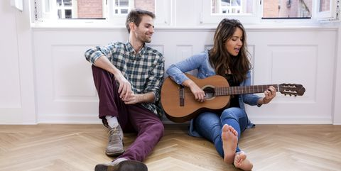 Young couple sitting on floor with woman playing guitar
