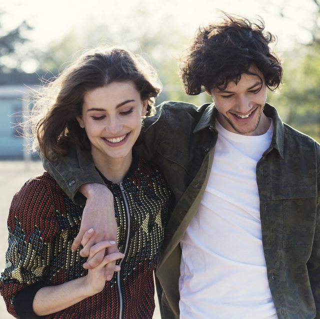 young couple smiling and walking in park