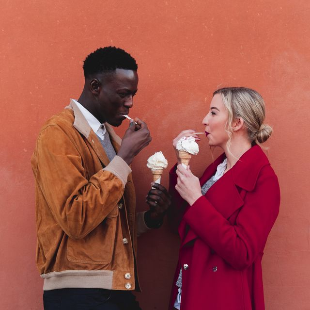 young couple standing at an orange wall eating ice cream