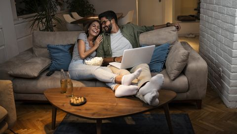 young couple watching a movie on a laptop