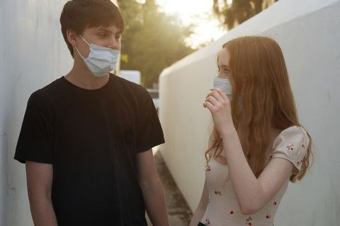 young couple wearing protective face masks in an empty city