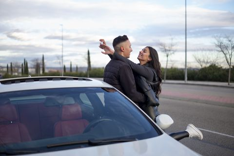 young couple with arm around standing by car