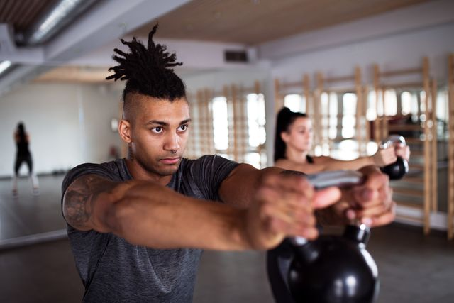 young couple with kettlebells doing exercise in gym