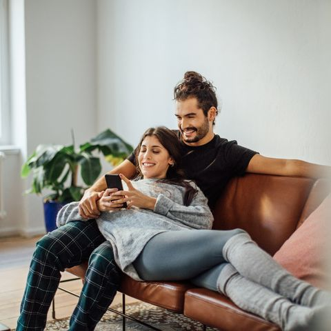 young couple with mobile phone relaxing on sofa
