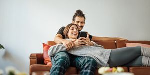 Young couple with smart phone relaxing on sofa