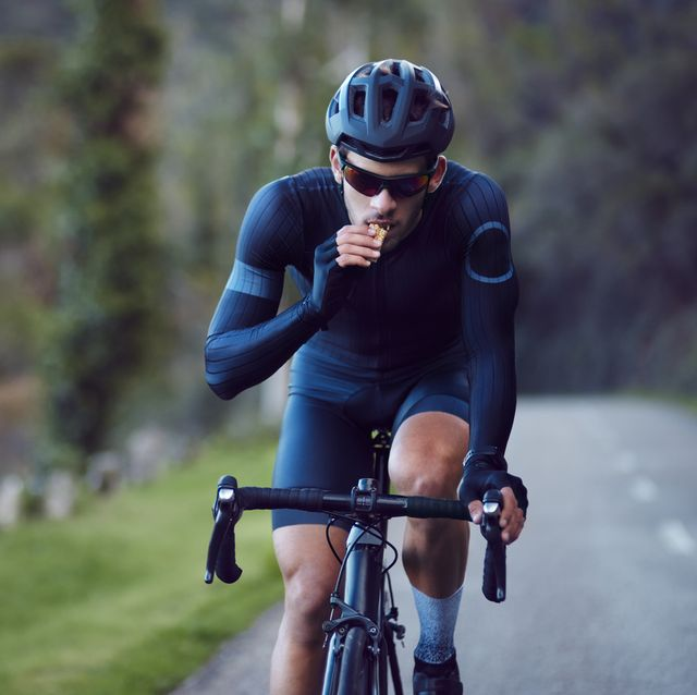 young cyclist riding bicycle and eating snack bar outdoors