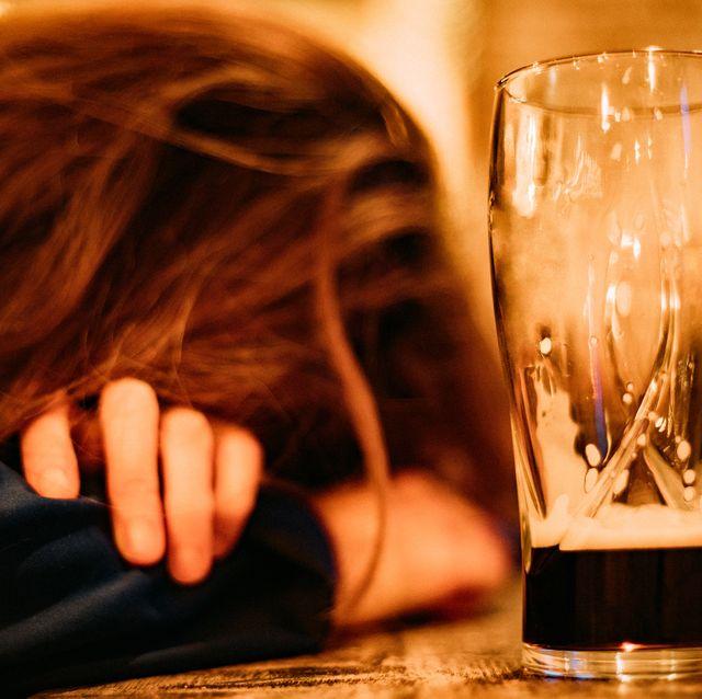 young drunk woman sleeping on bar counter drinking dark beer