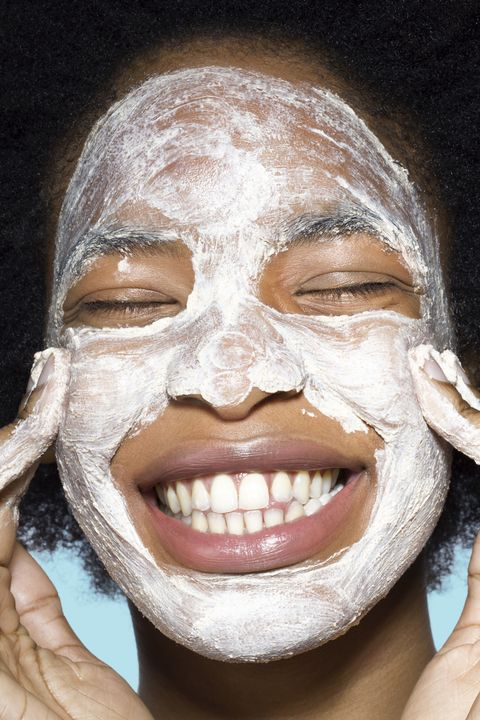 Young female applying face cream / mask