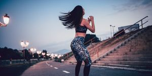 Young Female Athlete Doing Squats on Running Path