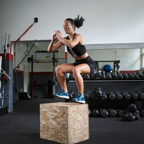 young female athlete jumping on a box at the gym