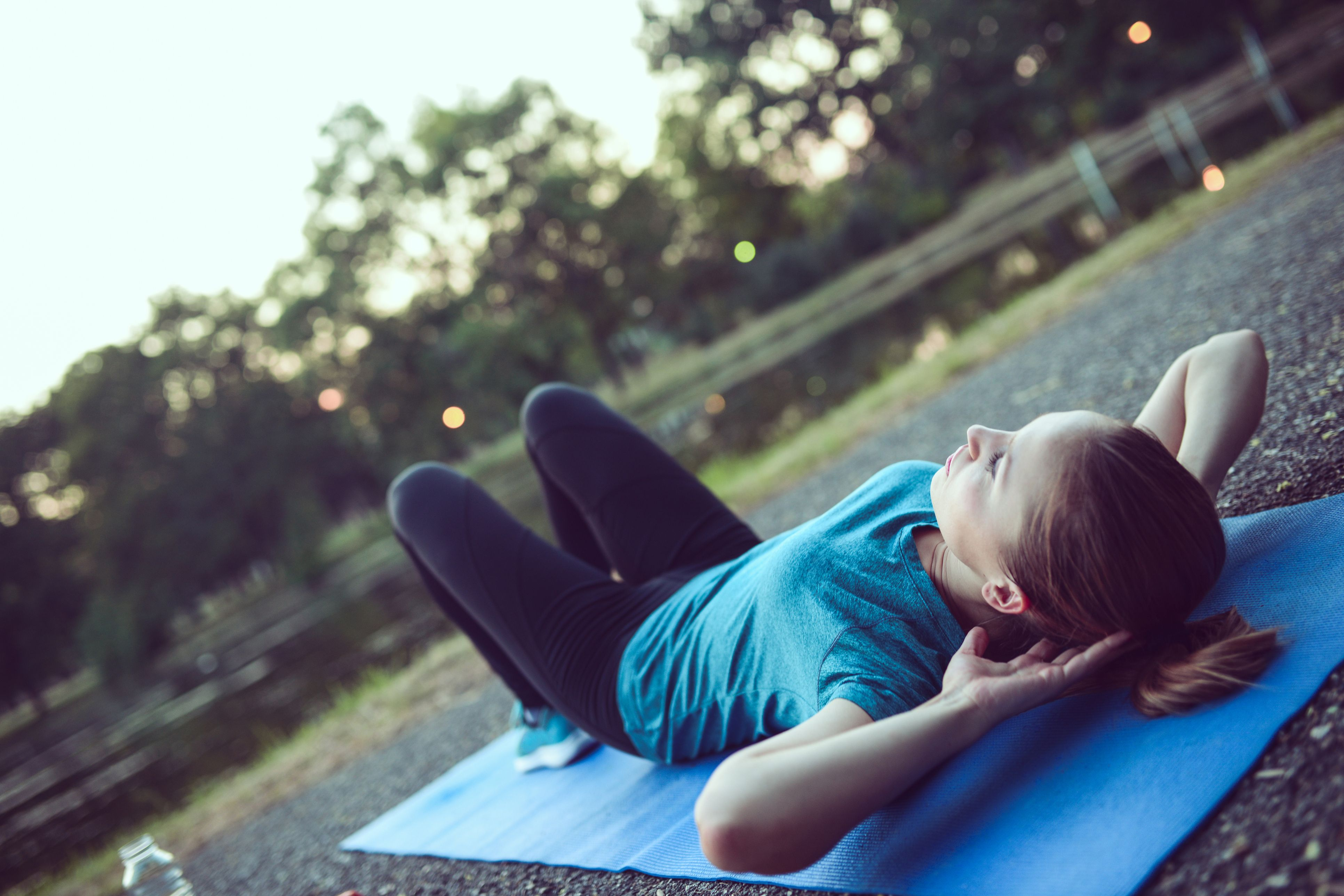 Young Female Athlete Performs Abs Crunches in City Park