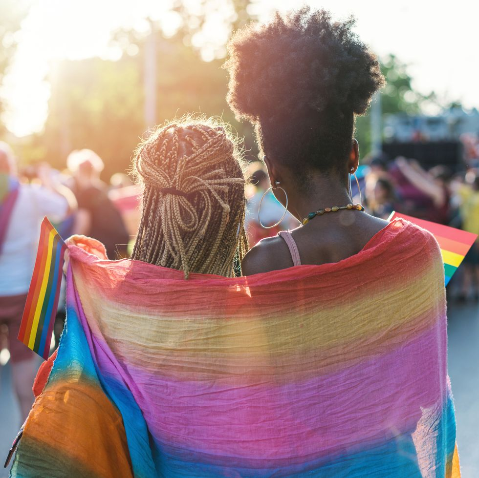 The picture focuses on two black women standing together in a side hug. They are both turned a way from the camera, and face a crowd of people. A big LGBTQ+ flag is draped around both of them, and each one holds a smaller flag.