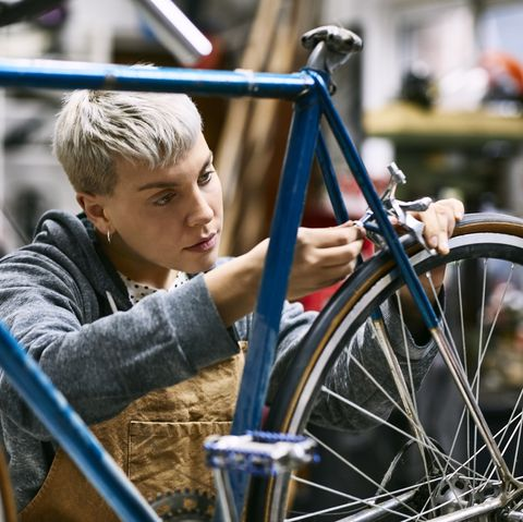 young female employee repairing bicycle brake