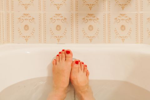 young female feet in bathtub