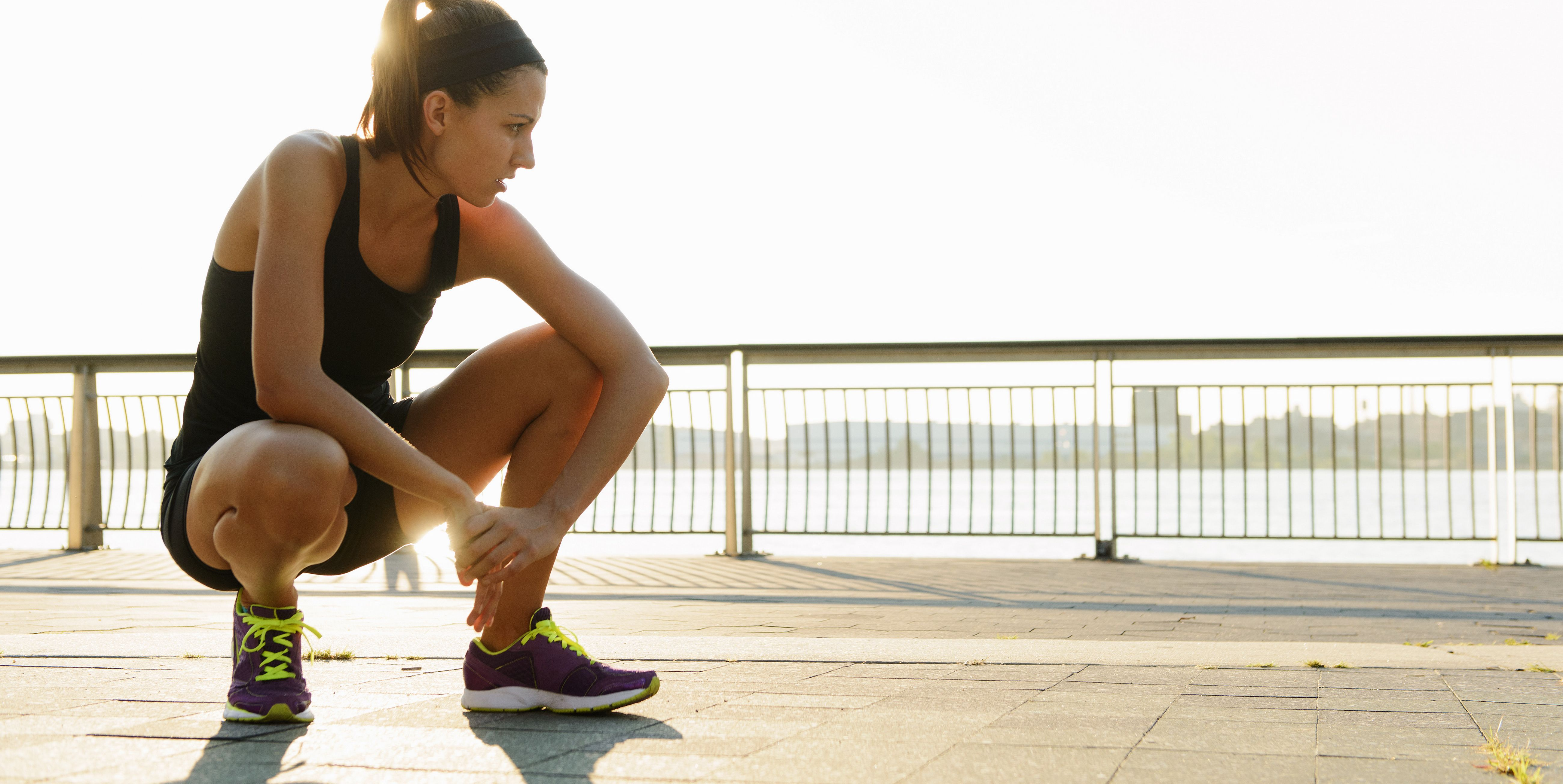 Young female jogger crouching and out of breath