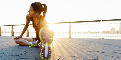 Young female jogger doing stretching exercise at sunrise