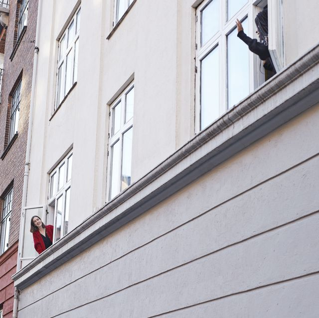young female neighbors waving and talking from apartment windows