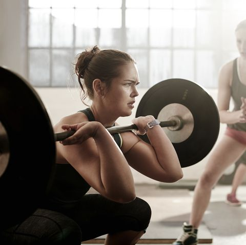 Young female working out with barbell