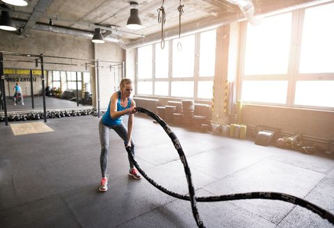 Jovens se encaixam mulher atraente no ginásio trabalhando seus braços e costas com barra de barra.